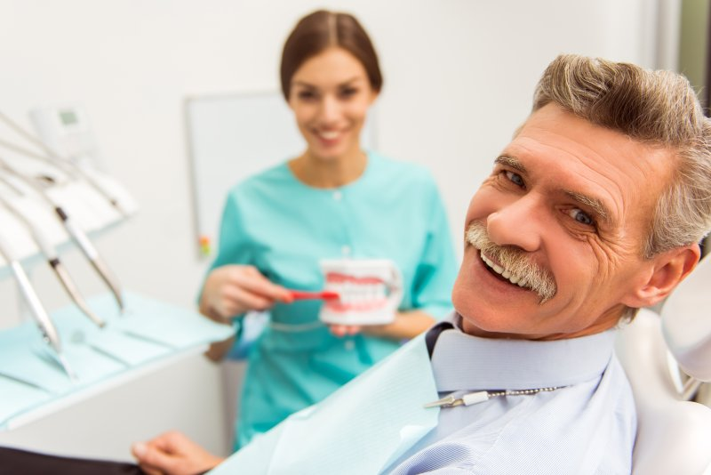 Dentist demonstrating to patient how to clean dentures