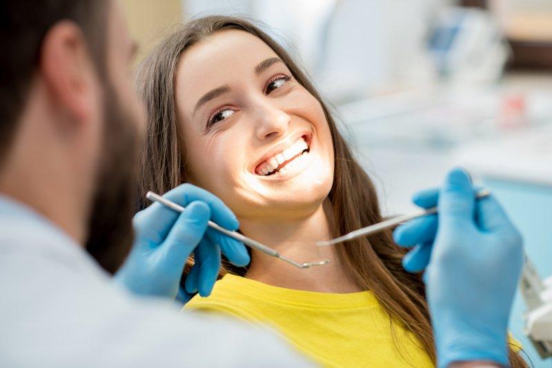 Woman smiling at dentist during dental checkup