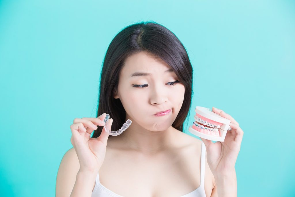Woman considering Invisalign vs. braces